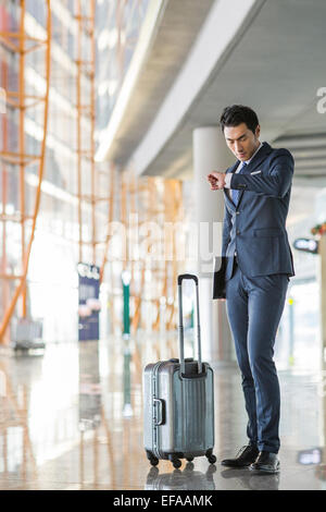 Young businessman checking time in airport - Stock Photo