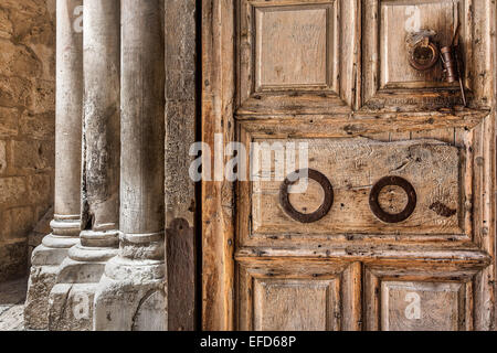 Ancient wooden door and marble pillars at the entrance to Church of the Holy Sepulcher in Jerusalem, Israel. - Stock Photo