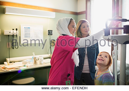 Nurse checking weight of girl in examination room - Stock Photo