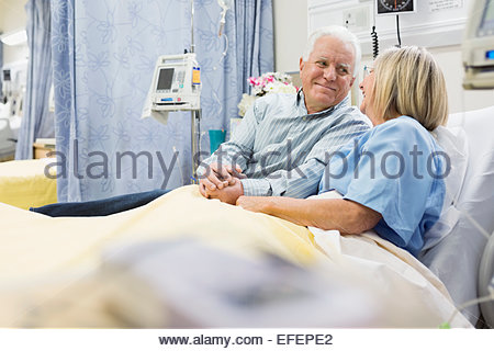 Husband and wife holding hands in hospital bed - Stock Photo