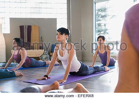 Women practicing upward facing dog pose yoga class - Stock Photo