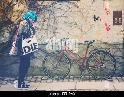 A street photograph of a girl with blue hair carrying a 'recycle or die' bag stopping to light a cigarette in Copenhagen - Stock Photo