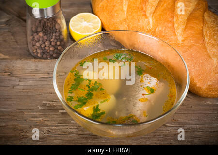 Tsar's fish soup in a glass dish on an old wooden table - Stock Photo