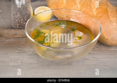 plate Tsar's fish soup in the morning mist on the old table - Stock Photo