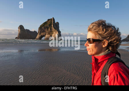 Woman on the beach on a windy day, Archway Islands in the background, Wharariki Beach, South Island, New Zealand - Stock Photo
