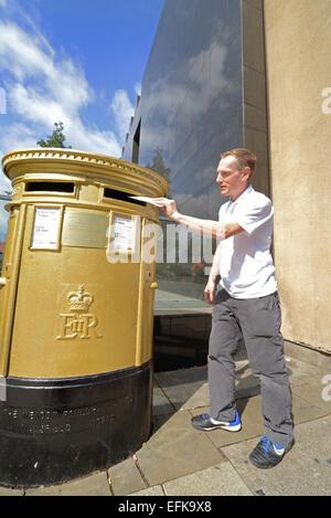 man using golden royal mail post box in leeds celebrating nicola adams winning boxing gold at the london 2012 olympics - Stock Photo