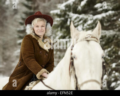 Attractive woman wearing a winter jacket and hat, she riding a white horse and she looks towards the camera - Stock Photo