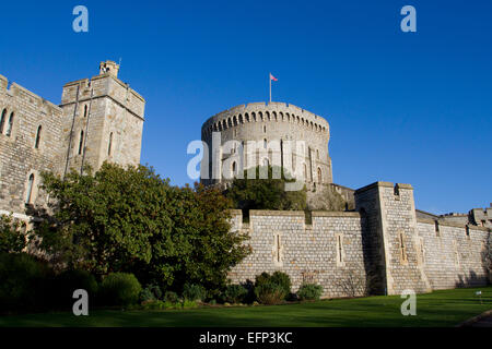 Round Tower (The Keep) and outer walls at Windsor Castle, Berkshire, England with Union Jack flying in January - Stock Photo