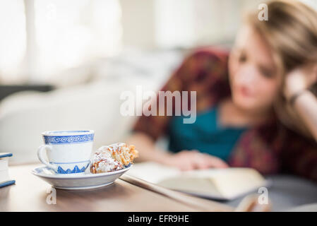 Young woman sitting on a sofa, reading a book. A cup and saucer with a croissant on a table. - Stock Photo