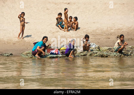 Horizontal view of a group of children playing and relaxing on the banks of the Mekong River. - Stock Photo