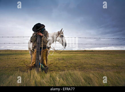 A cowboy standing leaning on a fence post on the range. A grey horse behind him. - Stock Photo