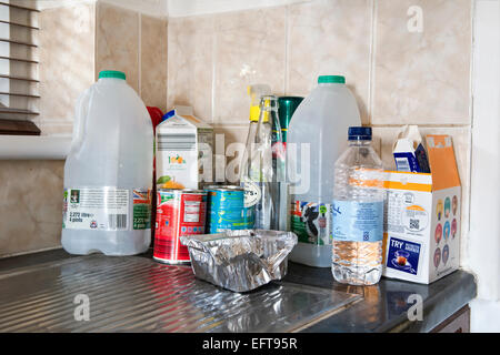 Re-cycling items including plastic, cans and tetra paks on kitchen top - Stock Photo