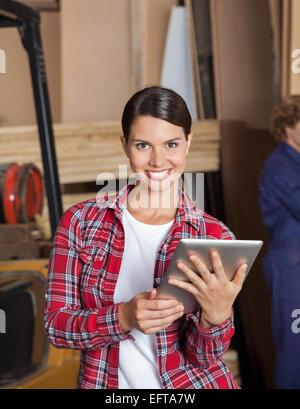 Confident Female Supervisor Holding Digital Tablet - Stock Photo