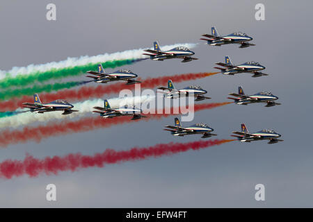 Italy's Frecce Tricolori aerobatic display team flying in formation and making smoke during an airshow display - Stock Photo