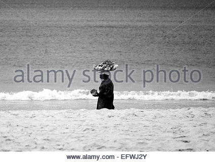 Fisherman Walking Along tropical Beach Carrying Plate Of Seafood On His Head United Republic of Tanzania TZA East - Stock Photo