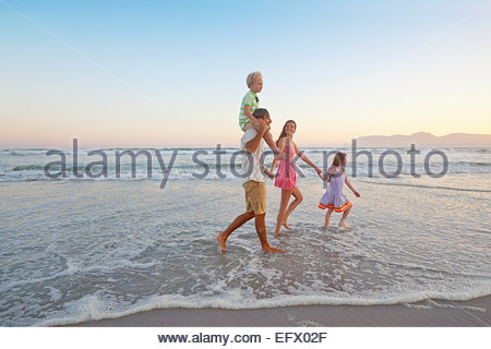 Happy family walking through waves, holding hands and son having piggy-back, on sunny beach - Stock Photo