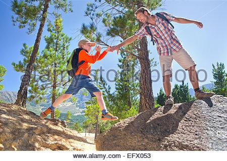 Father helping son climb, on mountain path - Stock Photo