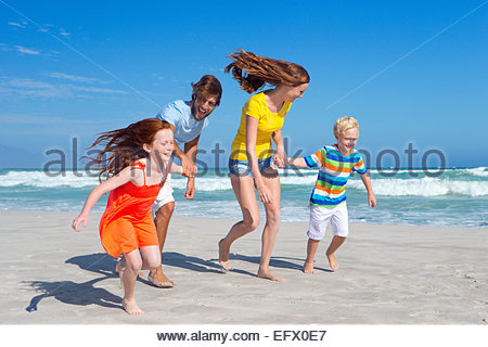 Happy family holding hands, running along sunny beach - Stock Photo