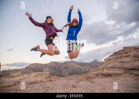 Two young female climbers jumping mid air on top of Smith Rock, Oregon, USA - Stock Photo