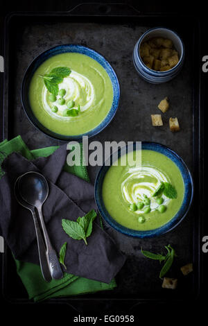 Pea soup served on a dark tray - Stock Photo