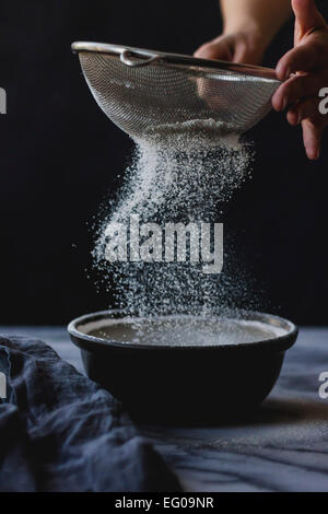 Sifting flour into a bowl whilst cooking - Stock Photo