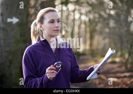 Woman Orienteering In Woodlands With Map And Compass - Stock Photo