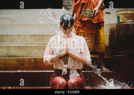 Cambodia, Buddhist monk water blessing young woman - Stock Photo