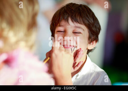 Bulgaria, Sofia, Young boy (4-5) getting his face painted - Stock Photo