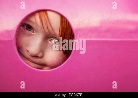 Young boy peeking through hole in playground tunnel - Stock Photo