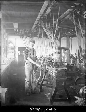 Antique c1910 photograph, boy machinist at machine shop, probably Massachusetts, USA. - Stock Photo