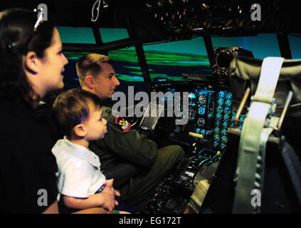 Capt. Mike Heddinger, 39th Airlift Squadron, shows Tracy Mitchell and her son James how to fly a C-130 simulator - Stock Photo