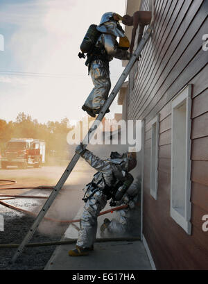 """Firefighters from the Ohio Air National Guard's 180th Fighter Wing rescue """"victims"""" from a burning building - Stock Photo"""