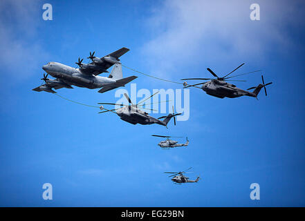 A U.S. Marine Corps C-130 left refuels two CH-53E Super Stallion helicopters under the watch of two AH-1 Cobras - Stock Photo