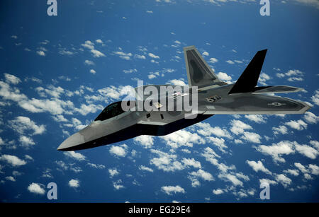 A U.S. Air Force F-22 Raptor fighter aircraft pulls away from a U.S. Air Force KC-135 Stratotanker aerial refueling - Stock Photo
