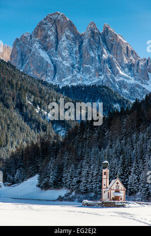 Scenic winter view over St Johann in Ranui mountain church with Puez-Geisler Dolomites behind, Villnoß or Val di - Stock Photo