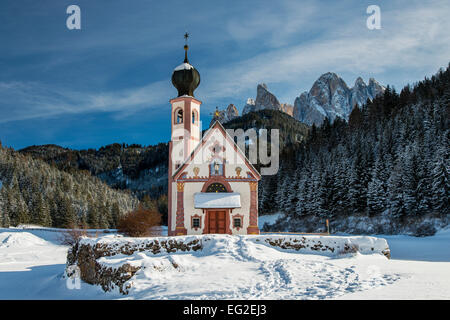 Scenic winter view over St Johann in Ranui mountain church with Puez-Geisler Dolomites behind, Villnoss or Val di - Stock Photo
