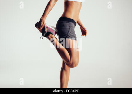 Cropped image of a fitness woman stretching her legs against grey background.  Fit female runner doing stretches. - Stock Photo