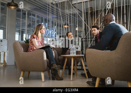 Diverse group of young people having a meeting in lobby. Young business executives meeting in office sharing creative - Stock Photo