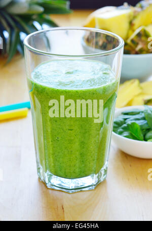 Green spinach and pineapple smoothie on table. Fruit smoothie made with baby spinach leaves, pineapple, banana and - Stock Photo