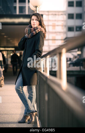 Full Length Shot of Stylish Pretty Young Woman in Autumn Fashion Leaning on Pathway Side Rails, Looking at the Camera. - Stock Photo