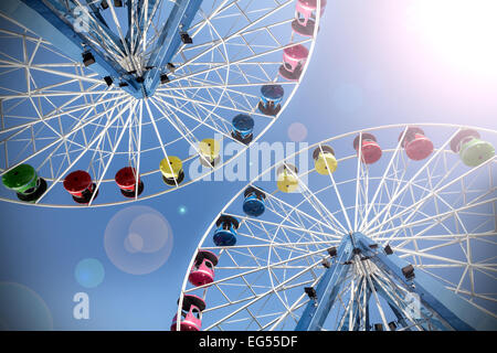Retro filtered picture of ferris wheels with lens flare. - Stock Photo