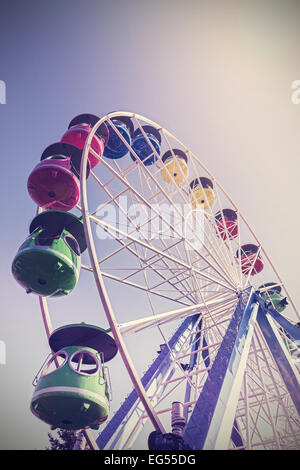 Retro filtered picture of ferris wheel in a park. - Stock Photo