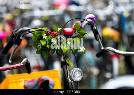 A Bicycle parked at Amsterdam's Amstel station decorated with flowers - Stock Photo