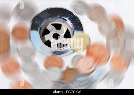 Wasted money going down the drain - Stock Photo