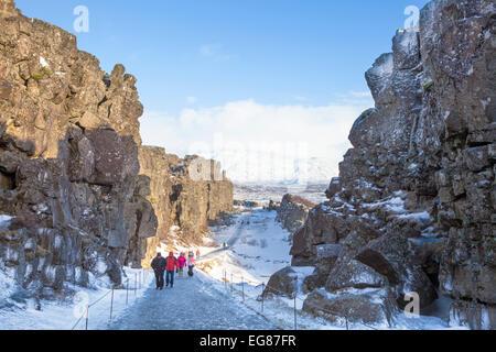 Tourists in the Allmannagja Gorge Þingvellir National Park in winter Iceland Europe - Stock Photo
