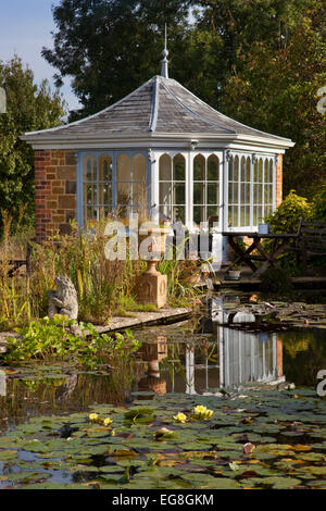 Large garden pond in summer with brick summerhouse and seating overlooking water and lillypads,Garden,Oxfordshire,England - Stock Photo
