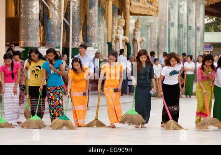 Young Burmese women sweeping the floor at sunset, Shwedagon Pagoda, Yangon, Myanmar ( Burma ), Asia - Stock Photo