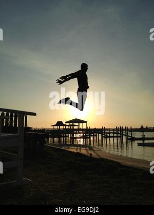 Man jumping high into sunset on beach - Stock Photo