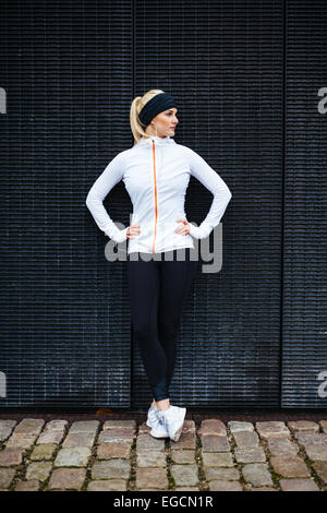 Full length shot of sporty young woman relaxing after running exercise. Female athlete resting after jogging in - Stock Photo