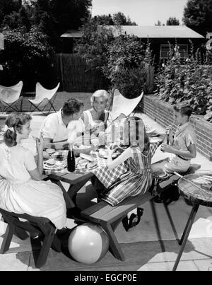 1960s FAMILY SITTING AT PICNIC TABLE IN BACKYARD EATING HAMBURGERS - Stock Photo
